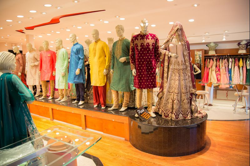 Mannequins in a store dressed in various traditional Indian jackets and saris